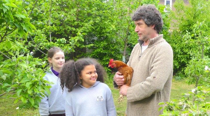 Little Green Fingers Hannah McDowell, 11, of Lauriston (primary) School Rutland Rd Hackney 270717 show one of the school's hens with gardener Steve Mason © DavidAltheer[at]gmail.com