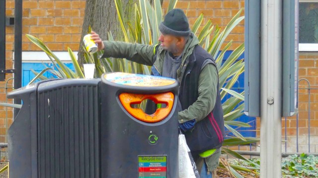 Homeless16; man checks recycle and other bin for food/drink remnants Amhurst Rd Hackney London E8 301216