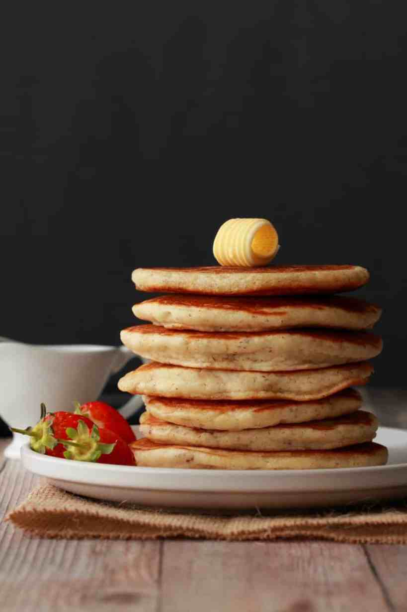 A stack of vegan pancakes with a pat of butter on top and strawberries on the side.