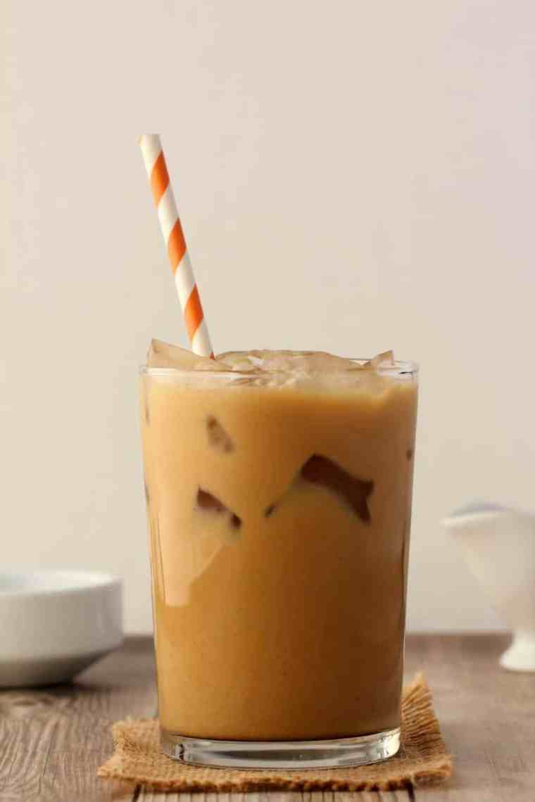 Vegan Iced Coffee in a glass with an orange and white striped straw.