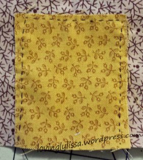 The yellow fabric is basted on top of the brown.