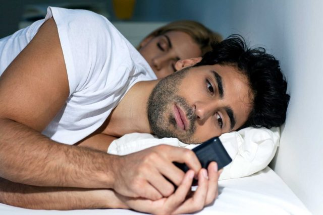 Man using iPhone in bed