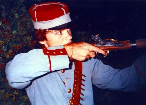 Simon of Businessmen On Bicycles posing with a prop flintlock rifle