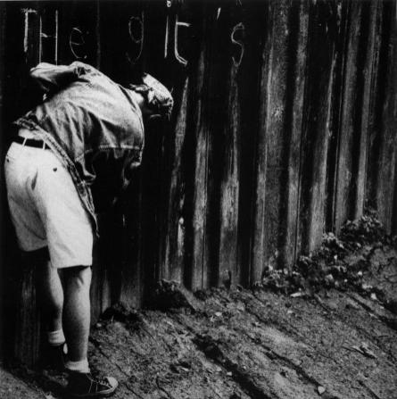 The front cover of the sleeve of The Gits' single which is a photograph of Ben bent over scrawling 'The Gits' on a corrugated building site support wall