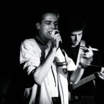 Black and white photo of The Gits in Concert at Champagnes Horsham with Jim singing holding a microphone in one hand and a cigarette in the other whilst Matt can be seen playing his Squier Telecaster over Jim's left shoulder