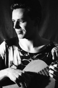 Jim posed with classical guitar with a slight smile, him not the guitar