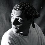 Portrait photograph of a bandana wearing Ben with face half in shadow looing behind him