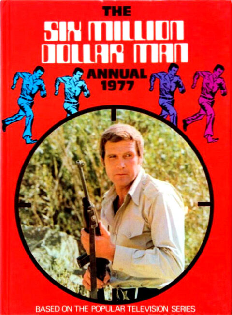 Front of the 1977 Six Million Dollar Man annual with the star Lee Majors holding a rifle and seen through a gun sight in the centre of a bright red cover