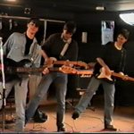 Rob, Matt and Ben stand on one foot whilst playing guitar
