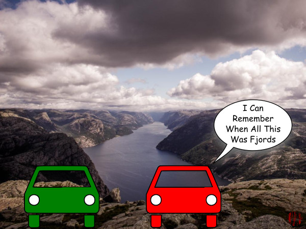 """Two cars are parked overlooking a long narrow glacier cut water way in Norway with one saying, """"I can remember when all this was fjords""""."""