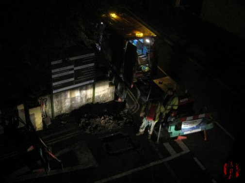 Men repairing a gas leak during the night as seen from above.