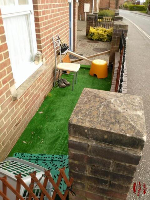 Photo of a small area between a fence and Council Flats where someone has laid a strip of artificial turf and placed a chair as a makeshift garden.
