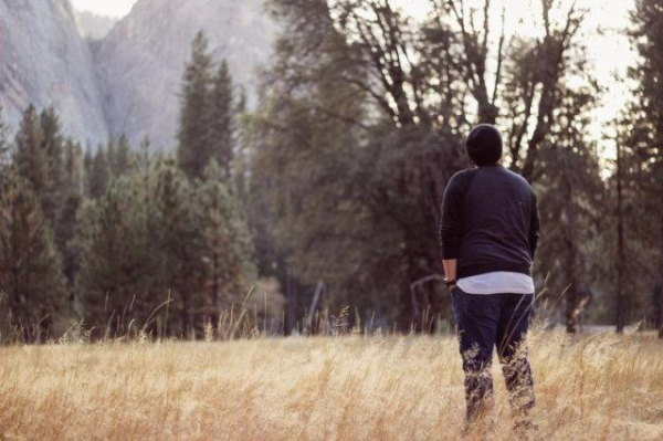 A chap stands slouchingly with hands in pockets in what otherwise would be a nice landscape