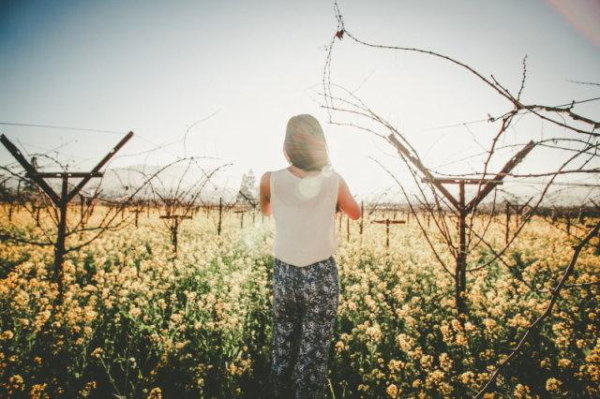 A sunny scene of flowers growing but for a woman in the way