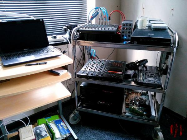 tea trolley with two and four track cassette players as well as MiniDisc and digital audio tape machines next to a desk with a laptop computer. Cassettes are scattered round about.