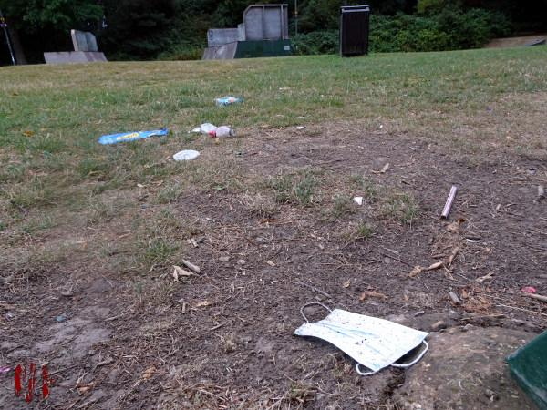 A view of Horsham Park seen over a discarded face mask and litter in the time of Coronavirus Covid-19.