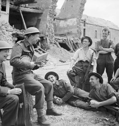 George Formby entertains troops in the ruins of a village