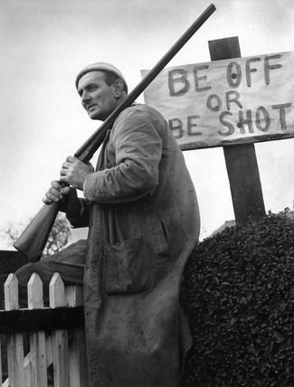 Farmer with gun sitting by Be Off or Be Shot sign 30