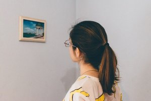 woman looking at photography in an art exhibition in a gallery