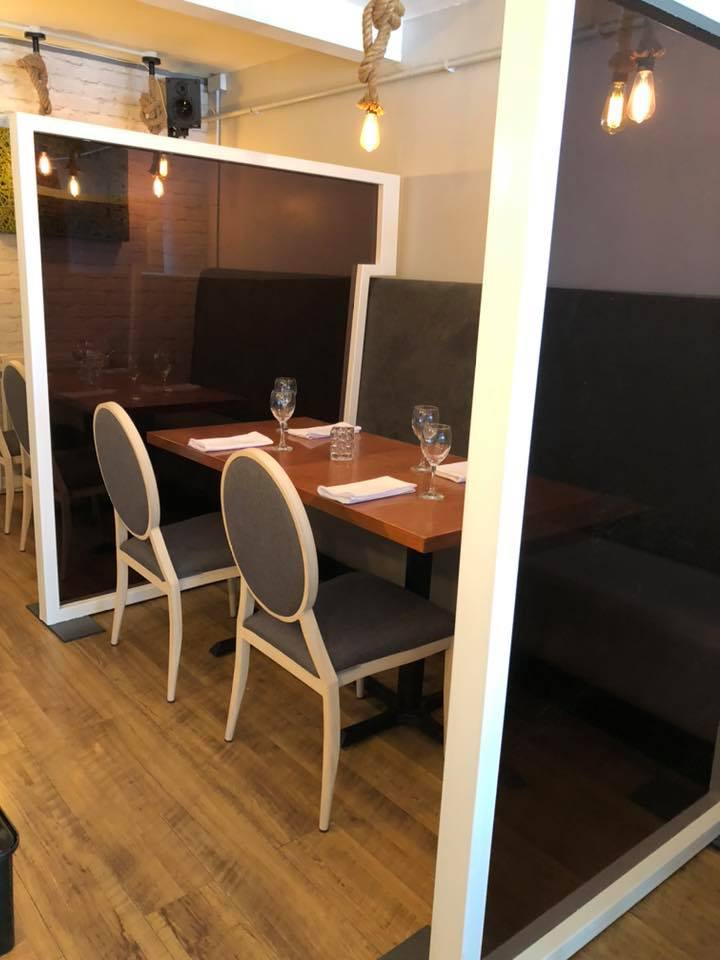 Screens divide up tables in Courtyard Bistro, Lowton, to enable social distancing for diners