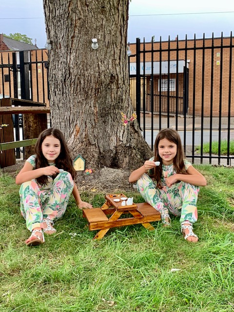 Young Golborne in Bloom Volunteers, Kaitlyn and Layla, sitting in the Fairy Garden they helped to create.