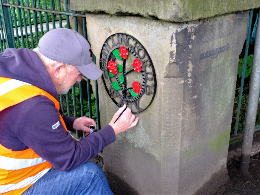 Alan Percival from Golborne and Lowton West Voice repainting the Millingford Brook sign.