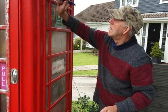 Brian Thilwind helps re-paint the former red telephone box on Slag Lane, now used as a defibrillator cabinet.