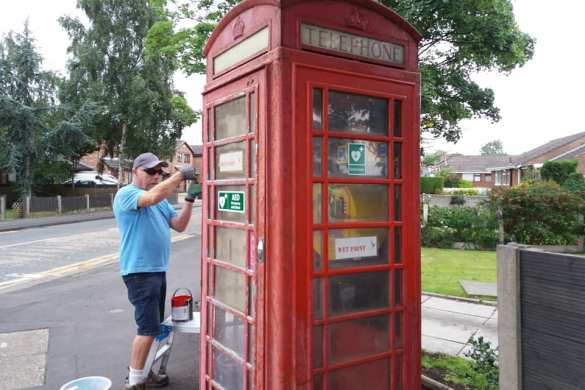 Stan Crook helps repaint the former red telephone box on Slag Lane, now used as a defibrillator cabinet.