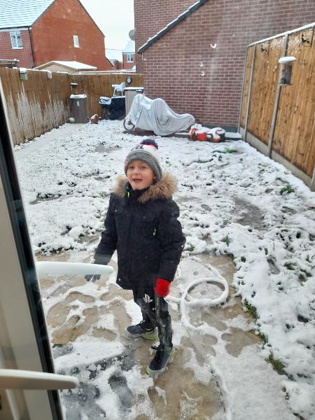 Boy plays in snowy back garden, taken by Debbie Ann