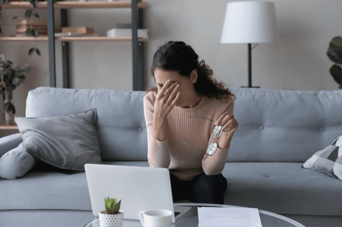 Woman sitting in front of laptop rubbing her eyes