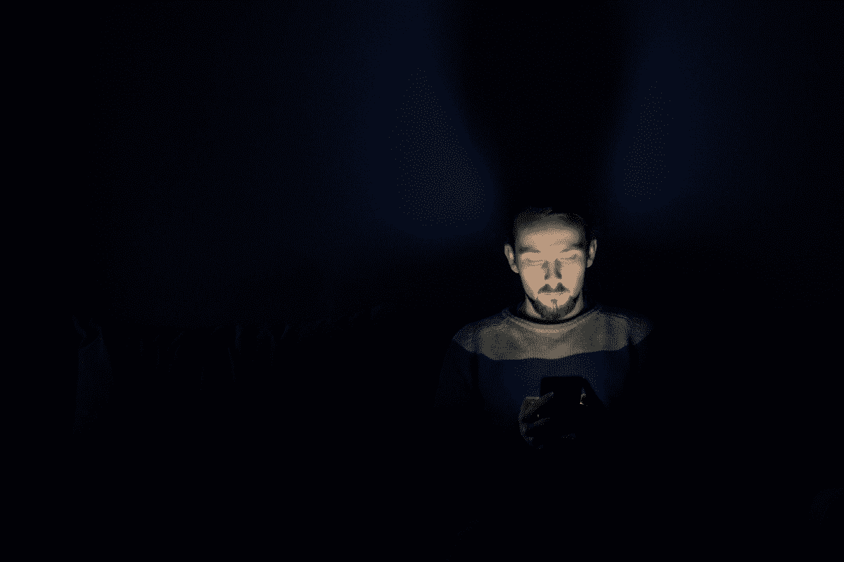 Man looking down at phone. Blue lighting can interfere with sleep and overall health.