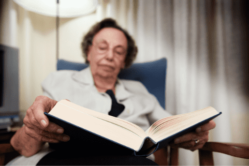 Senior adult reading a book. Library programming such as outreach programs have made books available to those stuck at home during the pandemic.