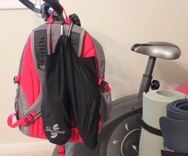 Black ShoeSling hooked to backpack on stationary bike