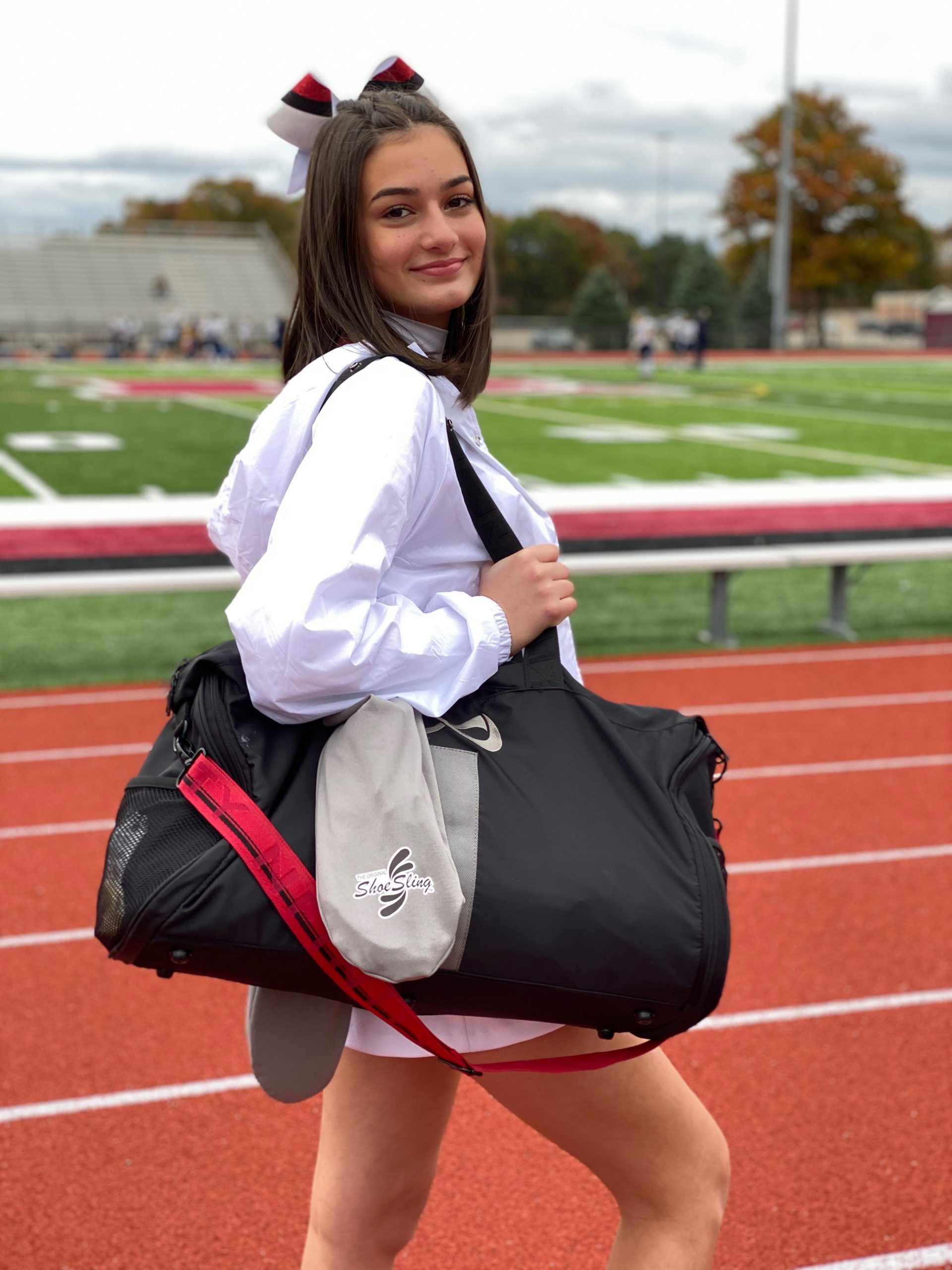 Young woman with titanium ShoeSling over gear bag at high school football game