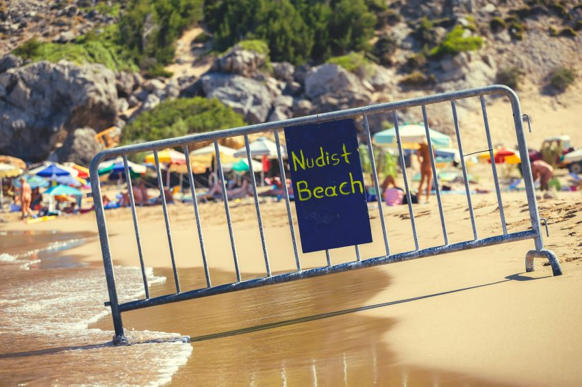 Nude beach sign with blurred nudists on the beach in the background