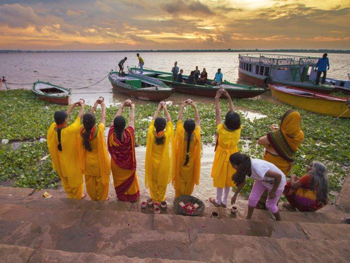 Women offer morning puja (prayers) beside the sacred river