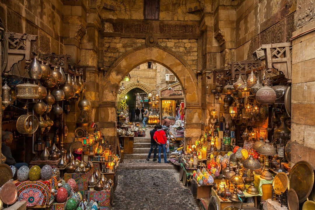 Lamps line the walls on either side of the path through the narrow market alleyway