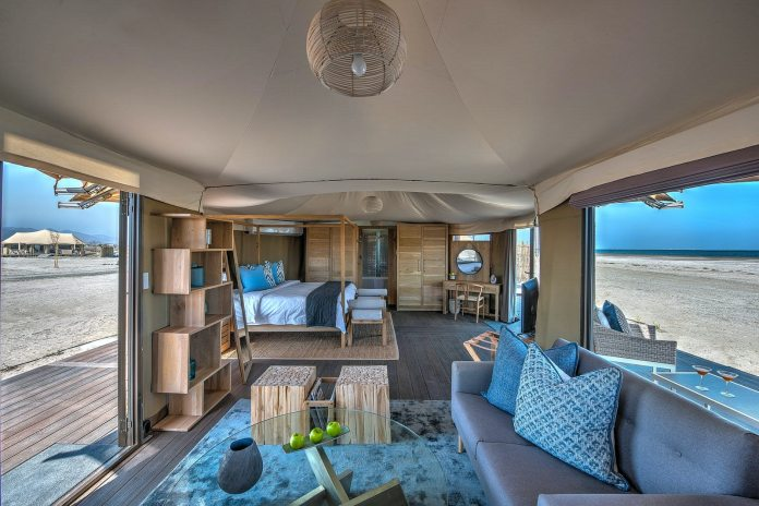 Blue and pine interiors of the Kingfisher Lodge glamping tent, including a couch, glass coffee table, double bed and bookshelves.