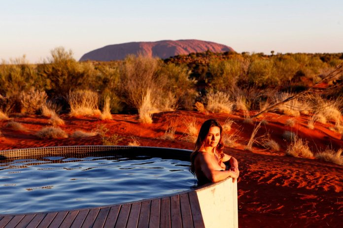 A woman sits in a hot tub with Australia's Uluru in the background.