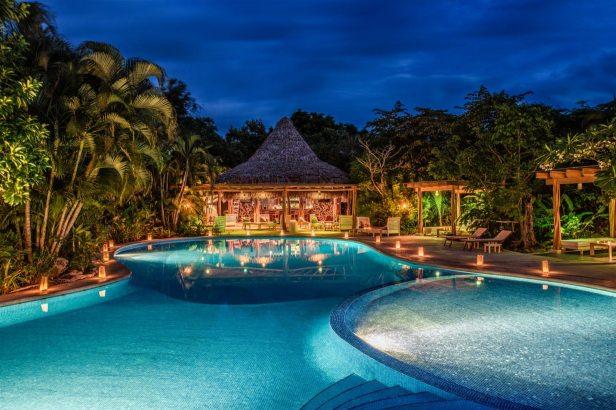 Una grande piscina trasparente circondata da piccole lampade si trova di fronte a un ristorante in legno a bordo piscina;  resort eco lusso