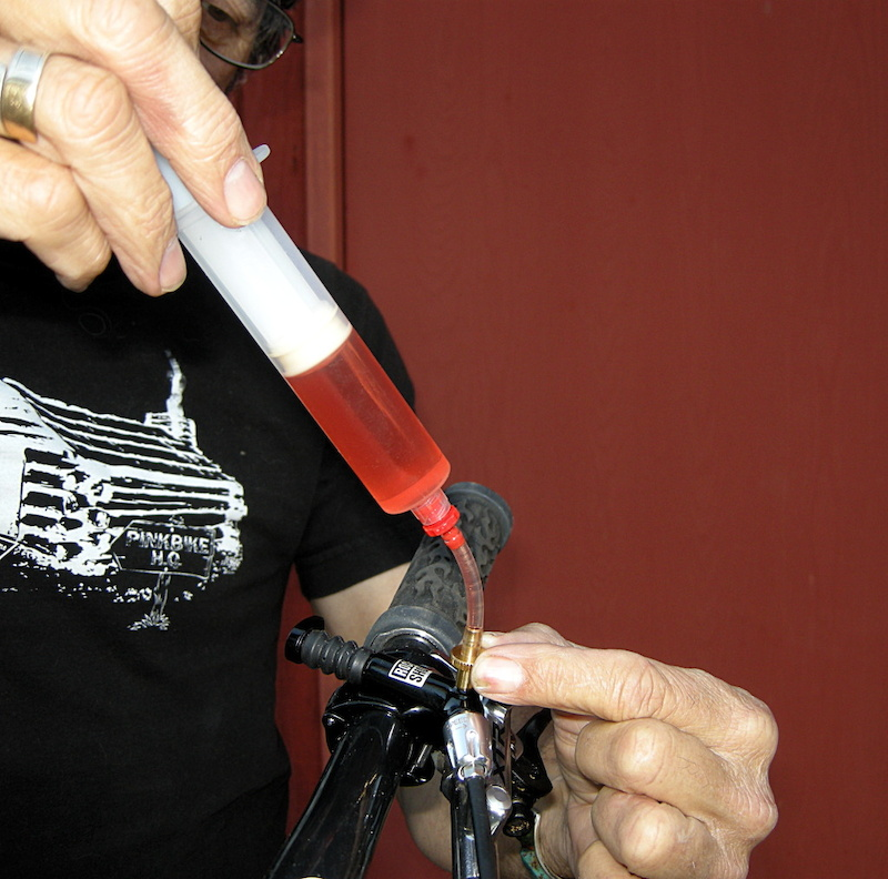 <span style='font-size:18px'>Step 8 - </span>Screw in full syringe to remote control bleed port.