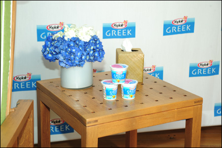 Photo of flower and yogurt cup arrangement on side table at Yoplait Greek Beverly Hills Event