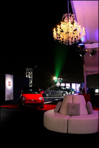 Photo of sporty cars parked on roof at night with chandeliers and circular lounge seats, carpeting for An Evening with Chrysler Group LLC