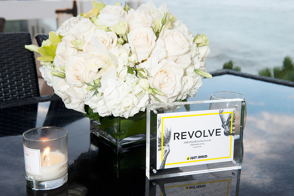 photo of elegant bouquet and Revolve Malibu Beach House placard with candles