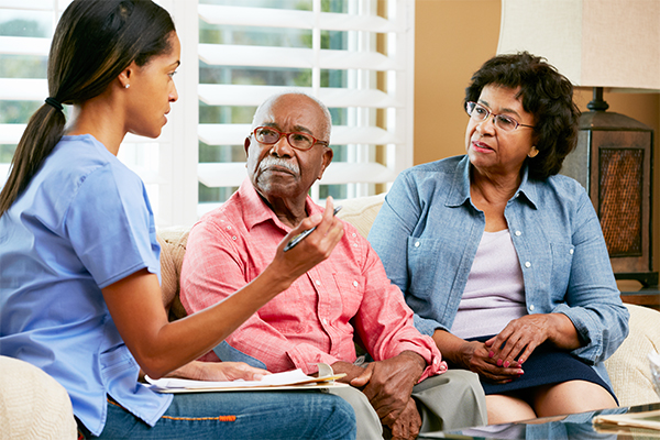 Nurse Making Notes During Home Visit With Senior Couple Talking To Each Other Sitting On Sofa