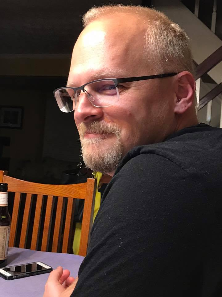 Photo of Kyle sitting at a table, looking over his shoulder at the camera. He is wearing glasses and has a slight smirk on his face.