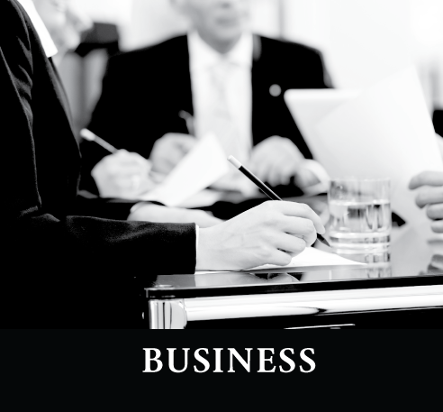business individuals sitting at table with pens and paper