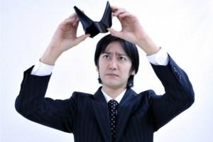 空の財布を掲げるスーツ姿の男性