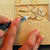 using a straight chisel to round over a relief wood carving