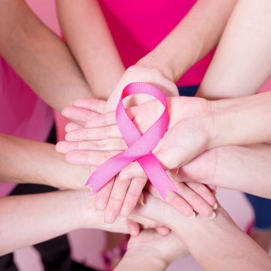 Image of a bunch of hands held together holding the breast cancer pink ribbon representing a unity of voices forming together to in the fight for breast cancer awareness.